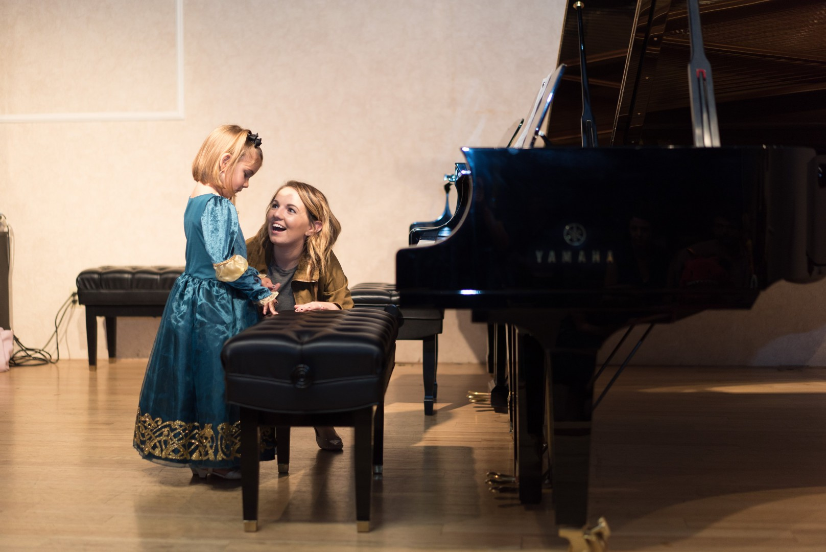 Instructor encouraging the little girl to play piano