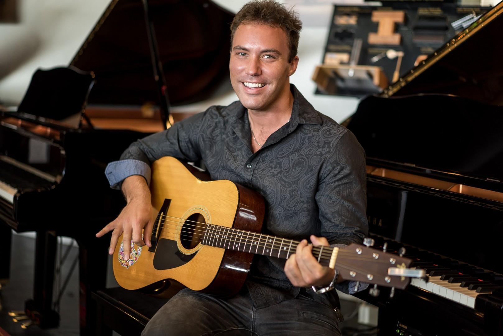 Man smiling while playing guitar at the same time