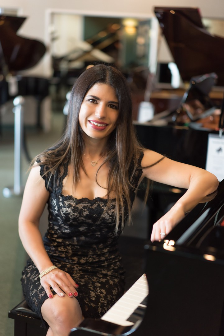 Woman smiling and sitting infront of the piano