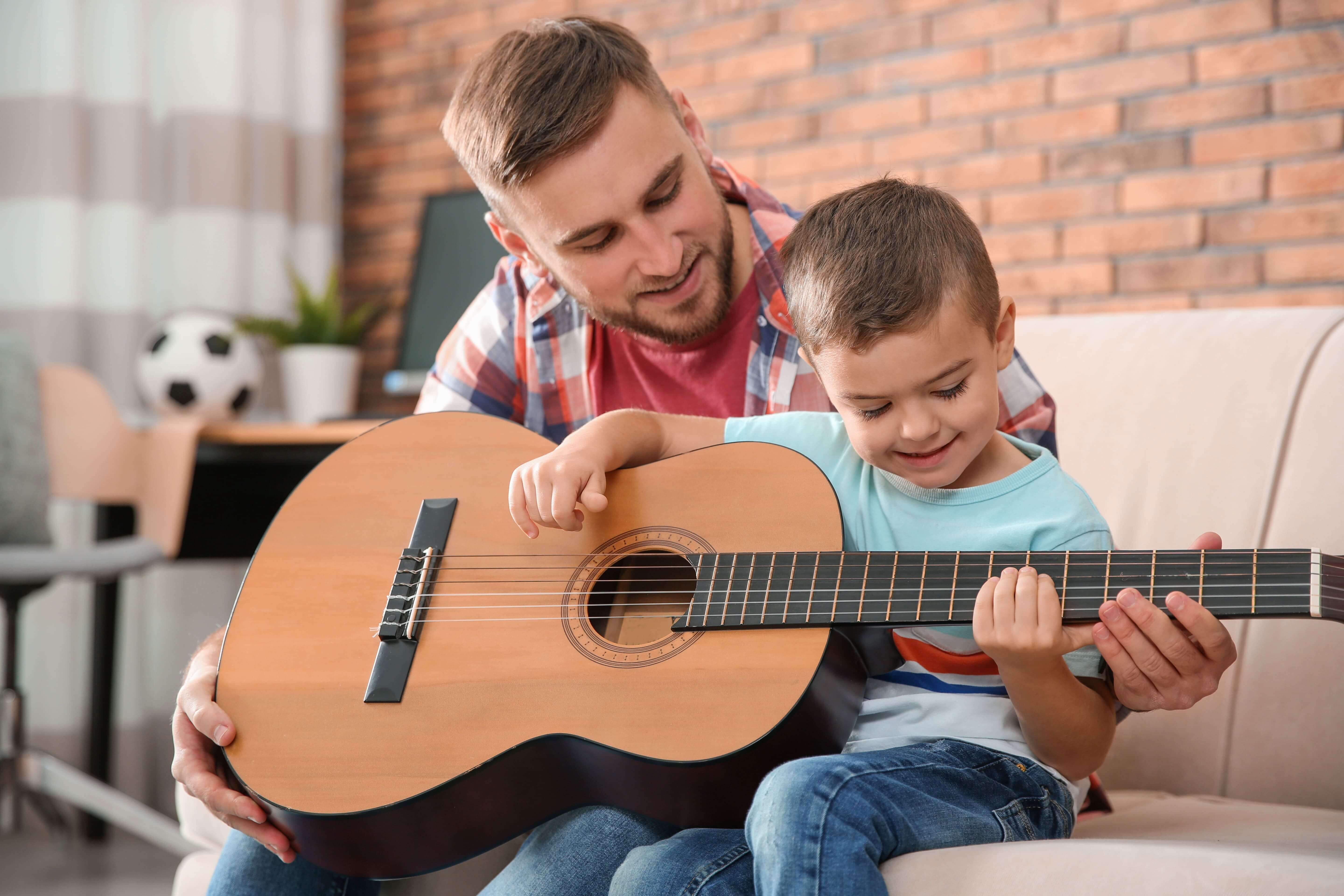 Instructor helping his student to play Guitar