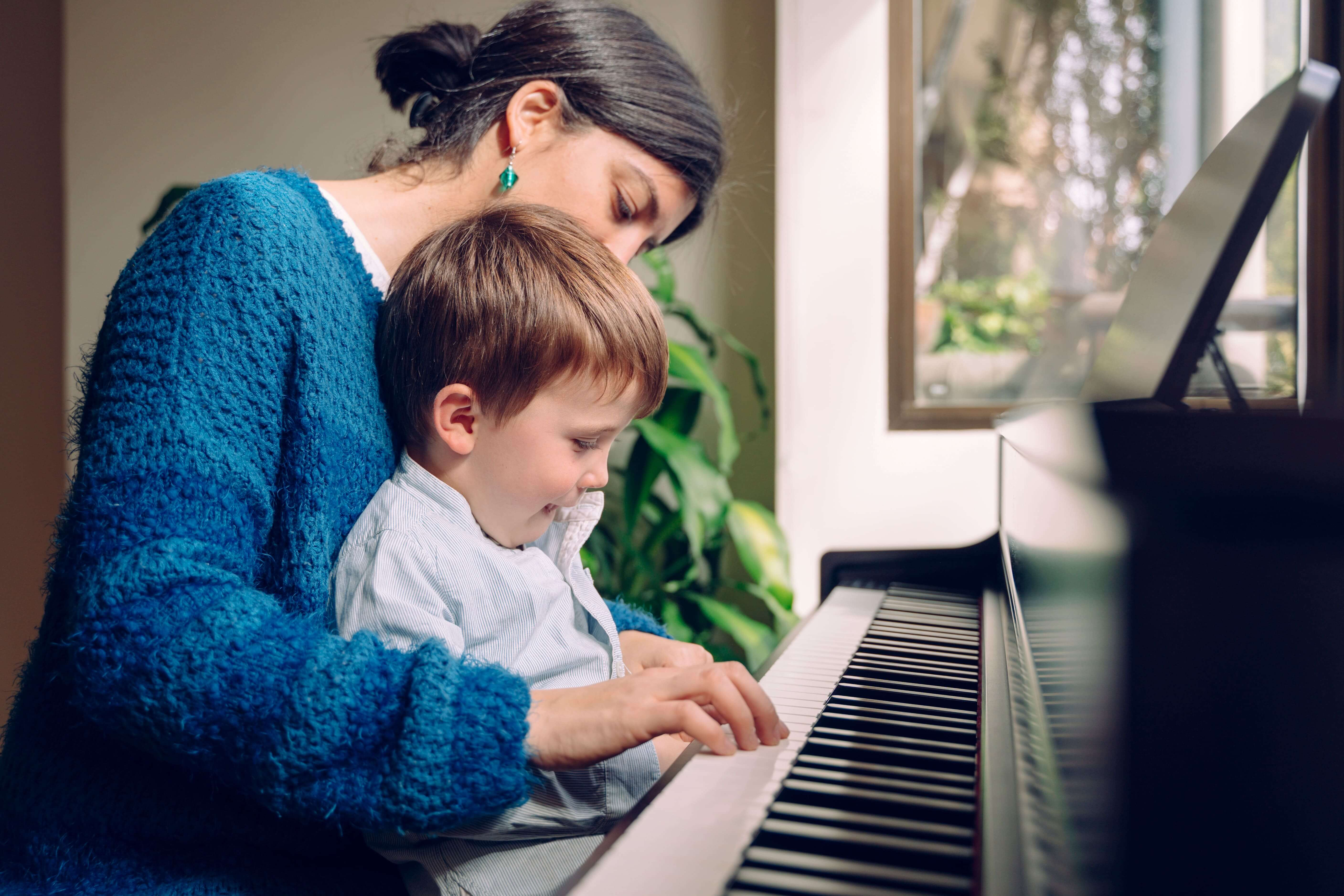 Instructor teaching her student on how to play Piano