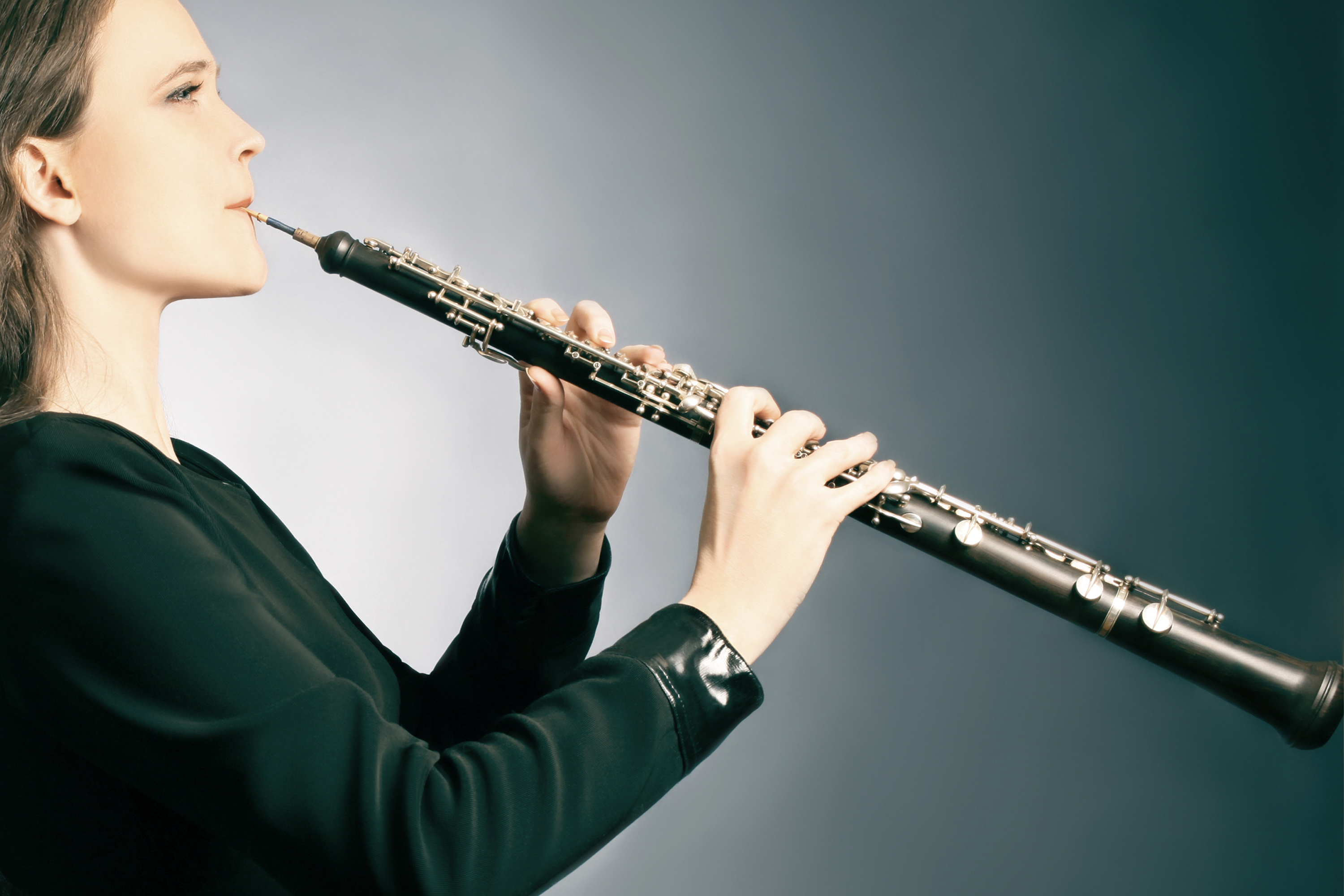 Woman graciously playing oboe windwood instrument