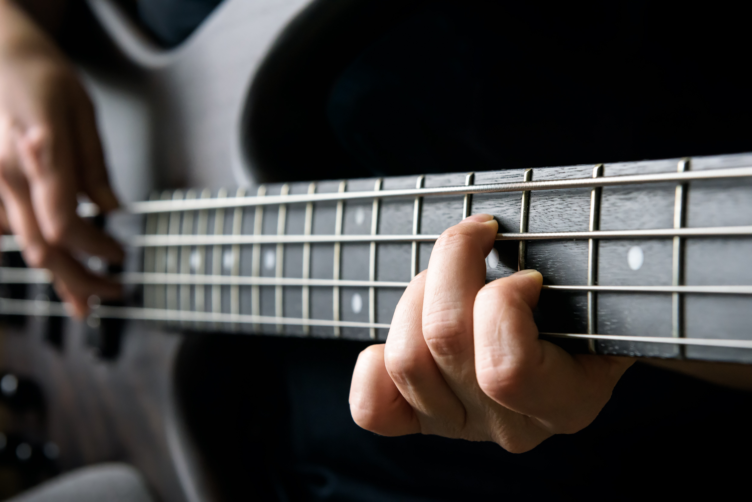 Student learning how to play bass guitar