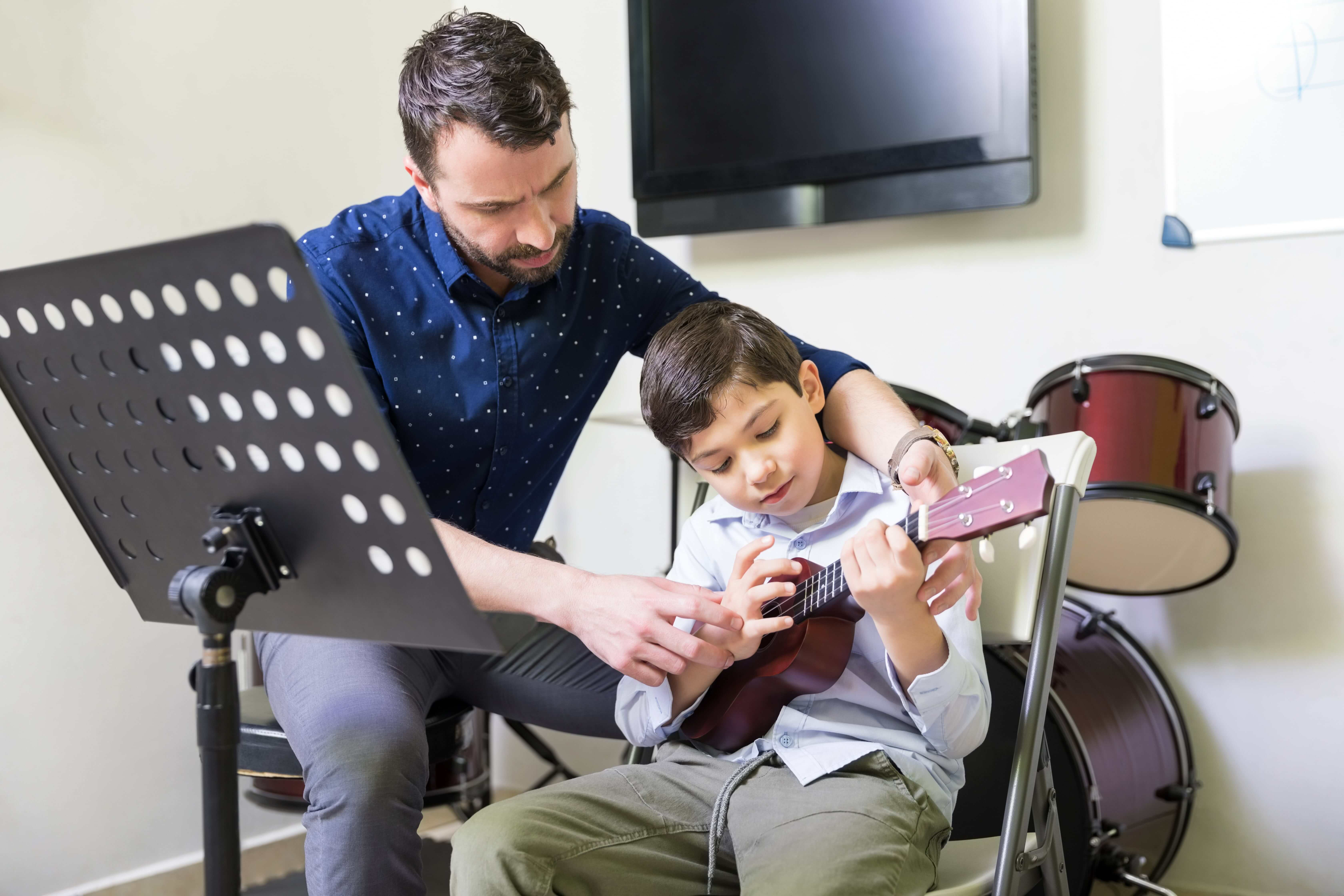 Instructor teaching his student on how to play Ukelele