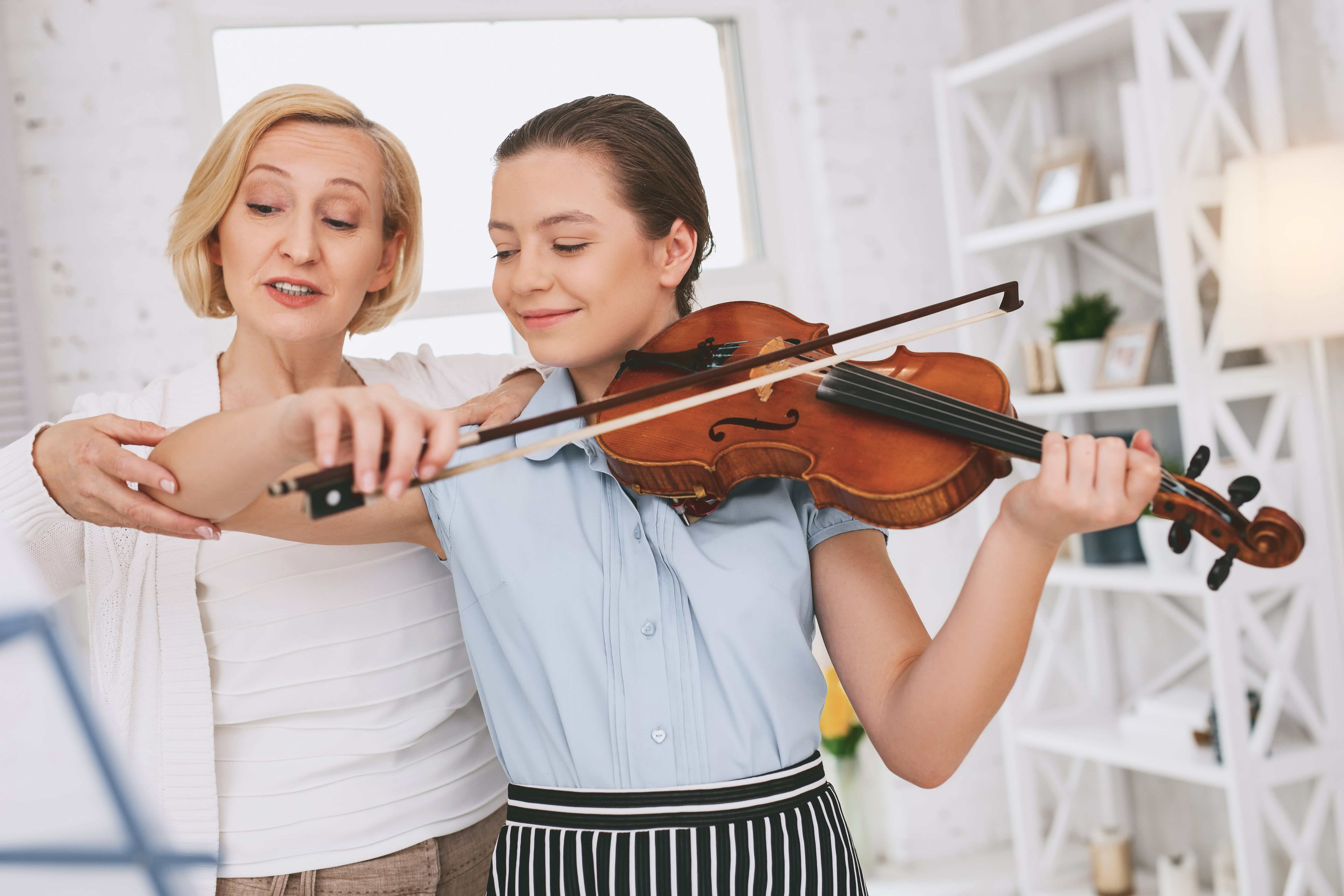 Instructor teaching her student Violin lessons